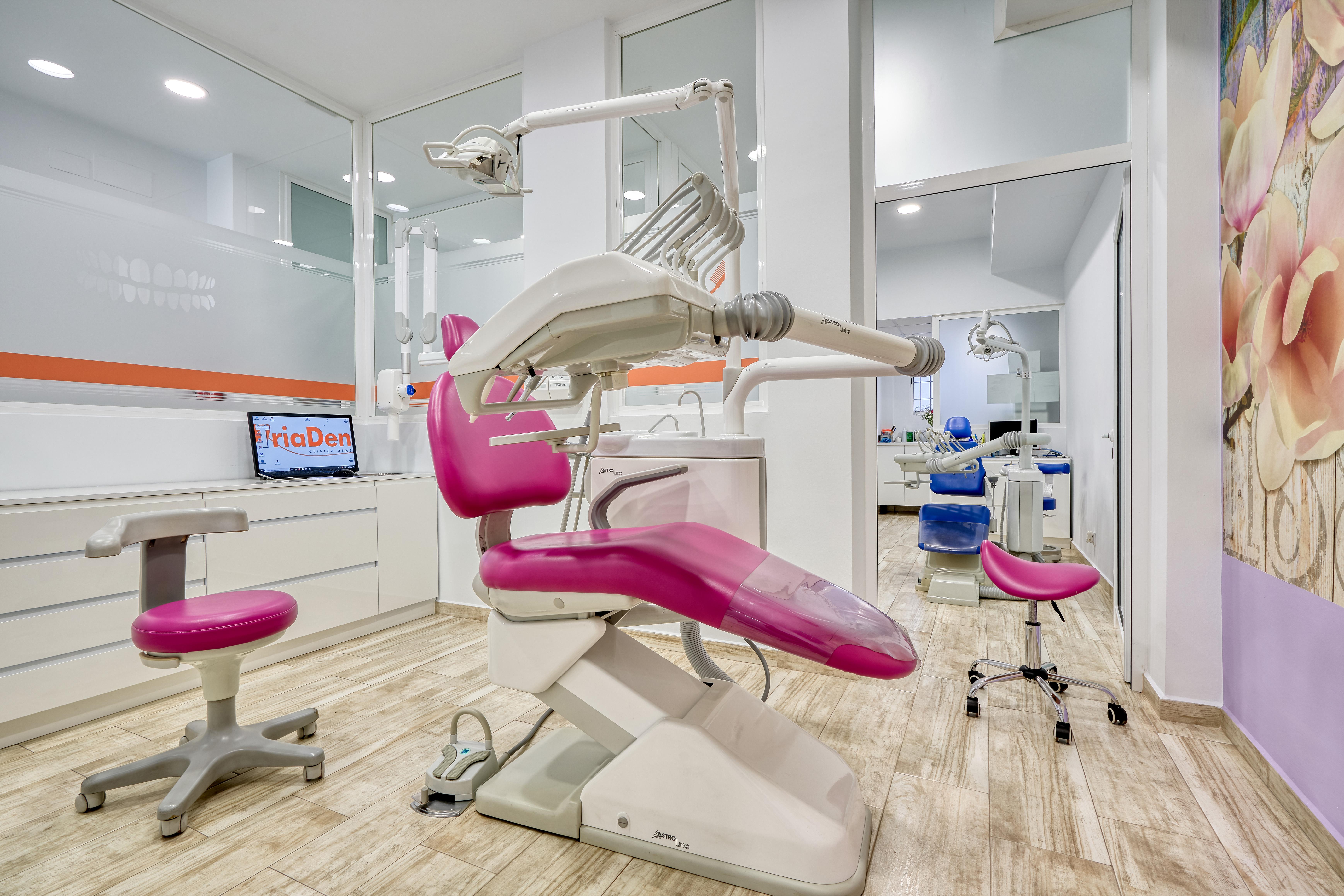 Gabinete rosa con sillón dental y mueble fijo con ordenador