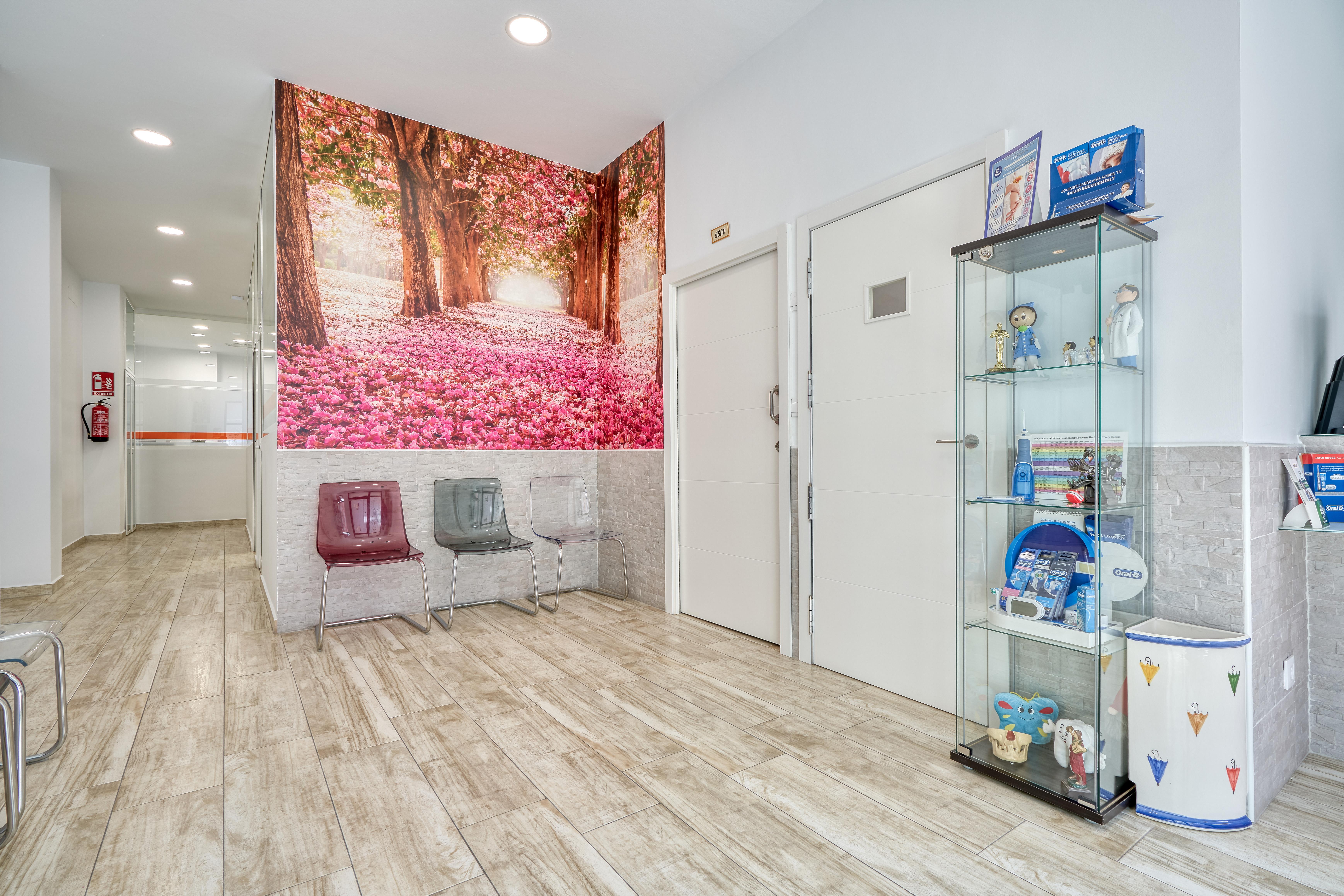Sala de espera con mural en la pared de un bosque con el suelo lleno de flores rosas
