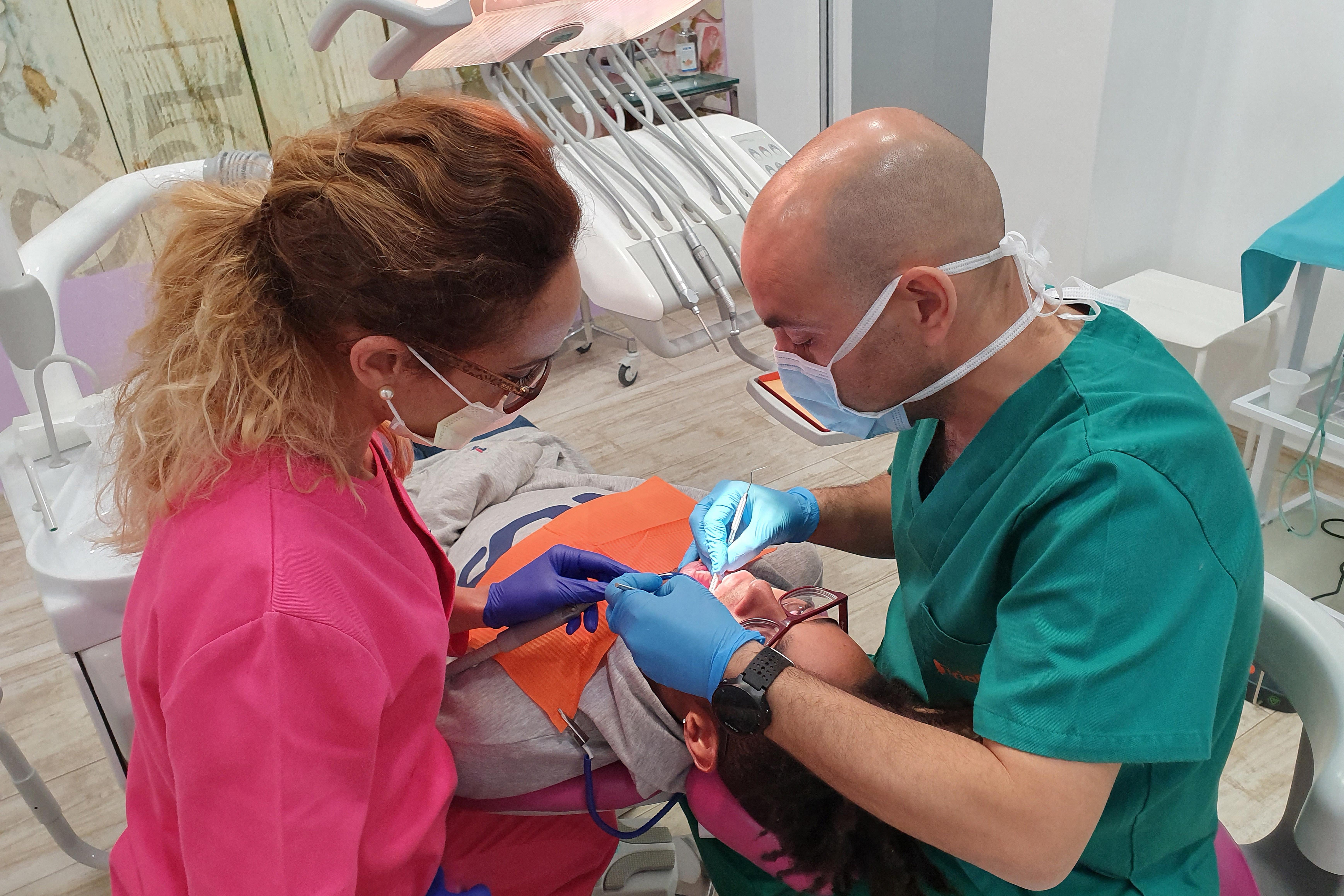 Dr Romero Fuentes e higienista Carmen Jiménez con paciente en gabinete